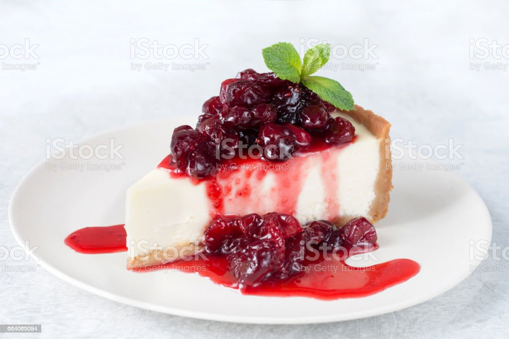 Plain cheesecake with cherry sauce on white plate