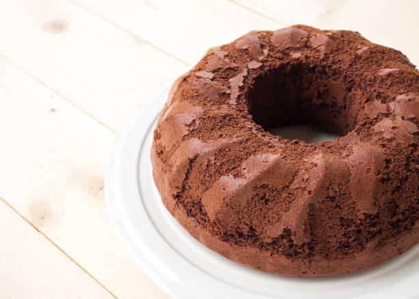 schlichte chiffon schokoladenkuchen auf weißen teller über holztisch. dessert-hintergrund. - biskuitboden stock-fotos und bilder
