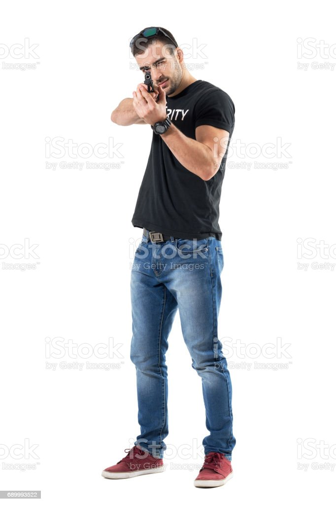 Plain clothes young policeman pointing gun with both hands aiming with one eye. stock photo
