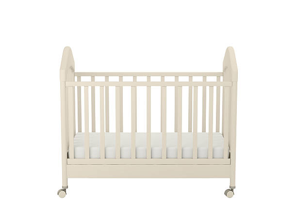 A plain cream colored crib with wheels White cot isolated on a white background crib stock pictures, royalty-free photos & images