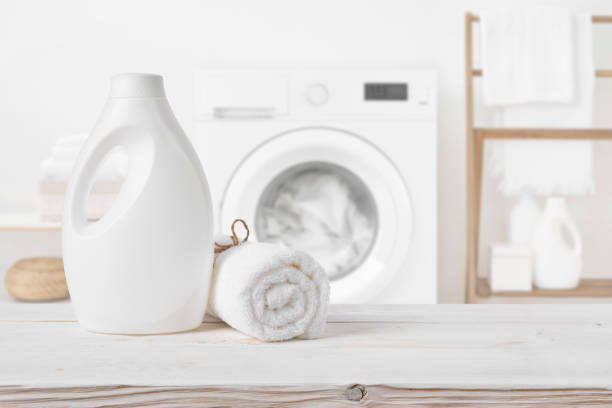 Plain detergent bottle on wood over defocused laundry room interior stock photo