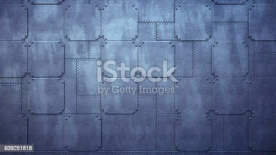 A direct frontal view on a factory wall made out of heavy metallic plates, held together with rivets. The image has an 16:9 aspect ratio.