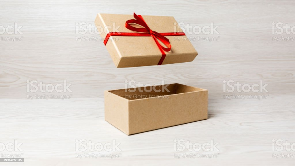 plain gift box, cover on the air with red bow on white wooden background foto de stock royalty-free