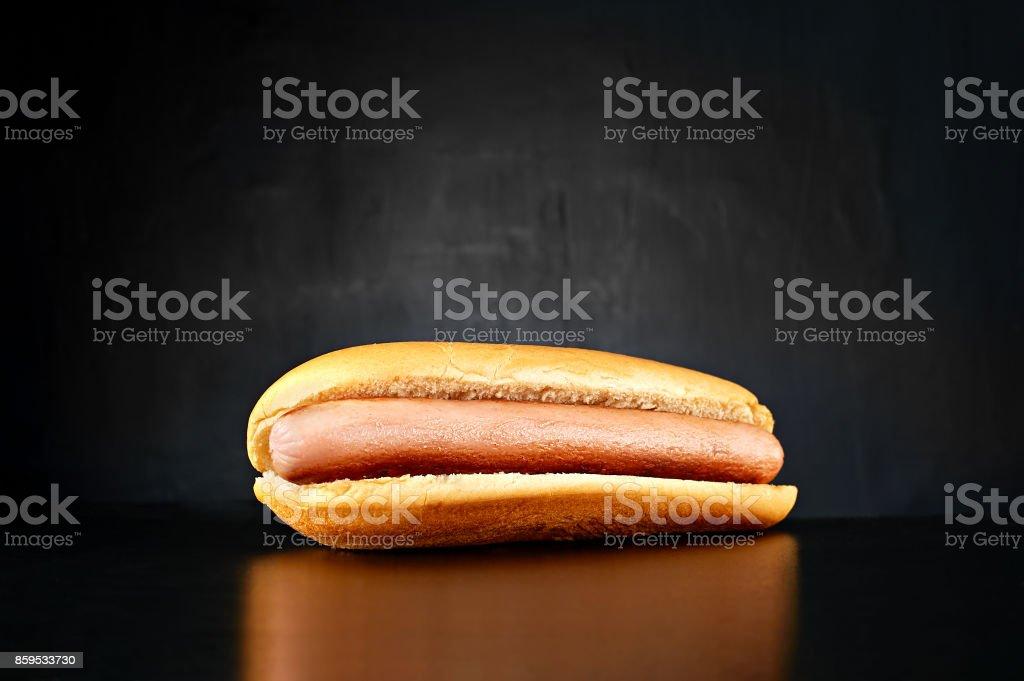 Plain hotdog with big sausage isolated on black background stock photo
