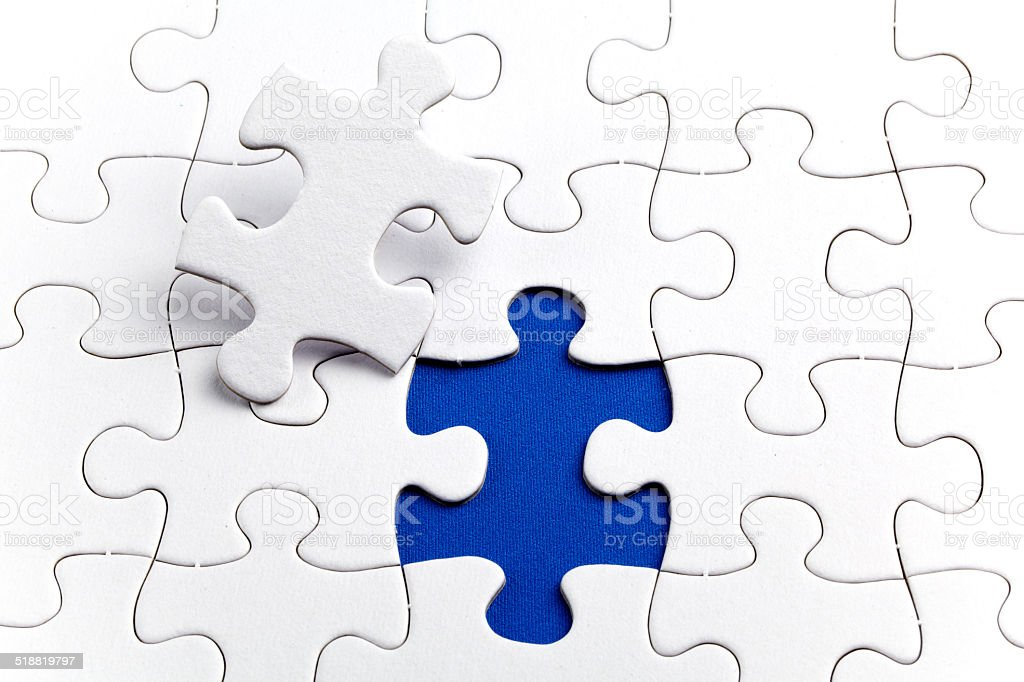 Plain white jigsaw puzzle, on Blue background stock photo