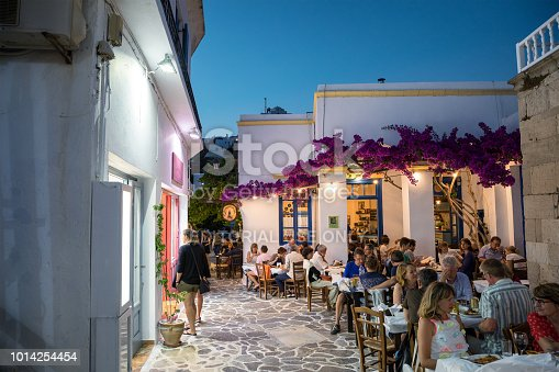 Milos island, Greece - June 11, 2018: Sunset scene in Plaka village which is full of shops and restaurants. People are dining in one of the restaurants decorated with bougainvillea flowers.