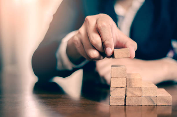 planen und strategie in der business.risk concept.hand des menschen hat sich aufstapeln und stapeln einen holzblock. geschäftsmann building the success. - mondlandefähre stock-fotos und bilder