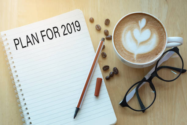 Plan for 2019 word on notebook with glasses, pencil and coffee cup on wooden table. Business concept. stock photo