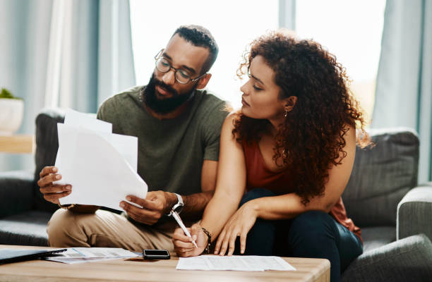Plan for the future you deserve Shot of a young couple going over their finances together at home home finances stock pictures, royalty-free photos & images