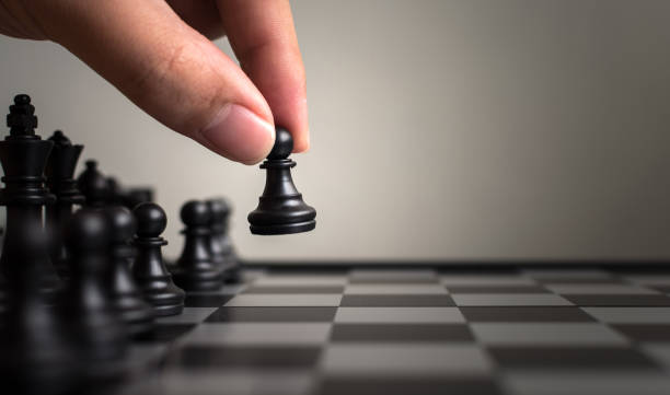 Plan leading strategy of successful business leader concept, Hand of player chess board game putting black pawn, Copy space for your text - foto stock