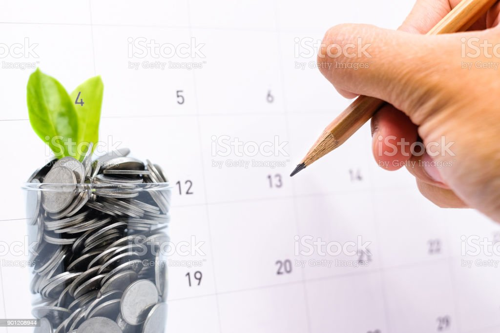 Plan to saving money in glass for your investment future is similar to growing green leaves on tree and write a message on calender for background or texture - economical & activity 2018 concept. stock photo