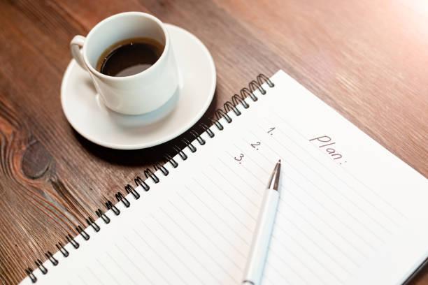 Planen Sie mit Liste und Kaffee auf Holztisch zu tun – Foto