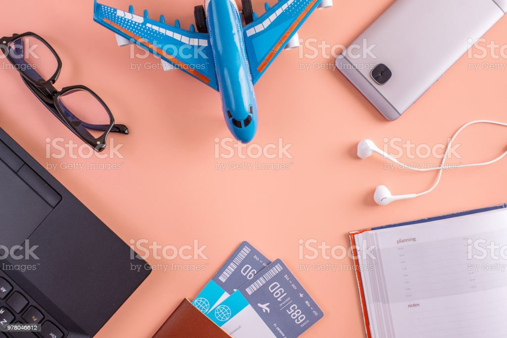 Plane, air tickets, passport, notebook and phone with glasses on pink background. The concept of planning for travel stock photo