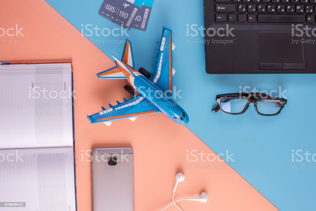 Plane, air tickets, passport, notebook and phone with glasses. The concept of planning and preparing for the travel stock photo