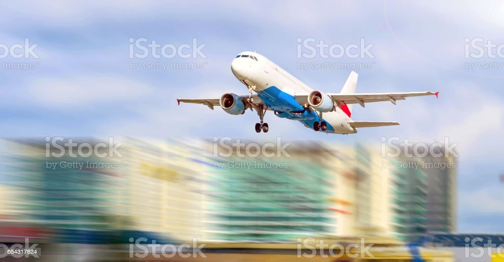 plane at the airport takes off against the background of the city and skyscrapers stock photo
