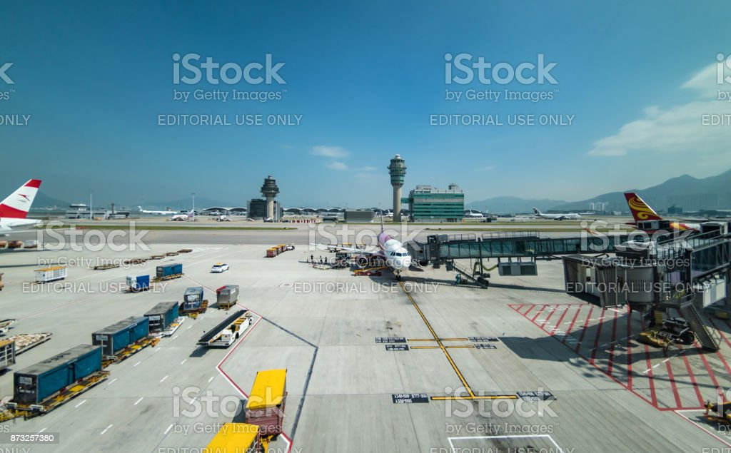Plane being boarded at Hong Kong airport with the air traffic control tower stock photo