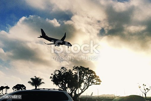 864534880 istock photo A plane comes in for a landing at sunset 1087746312