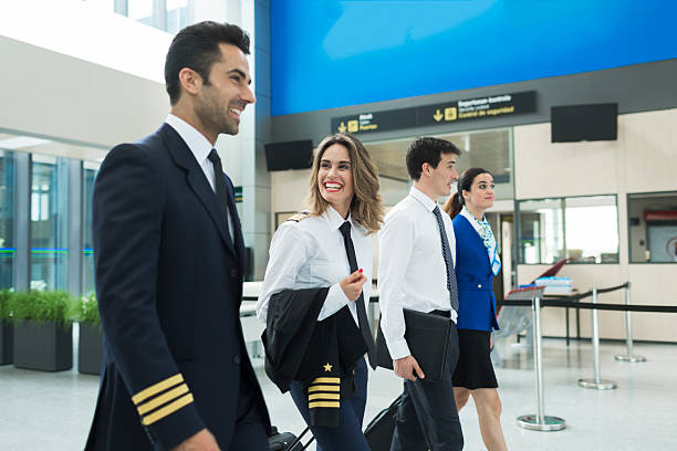Plane crew walking in airport terminal near airline office. Plane crew walking in airport terminal near airline office. cabin crew stock pictures, royalty-free photos & images