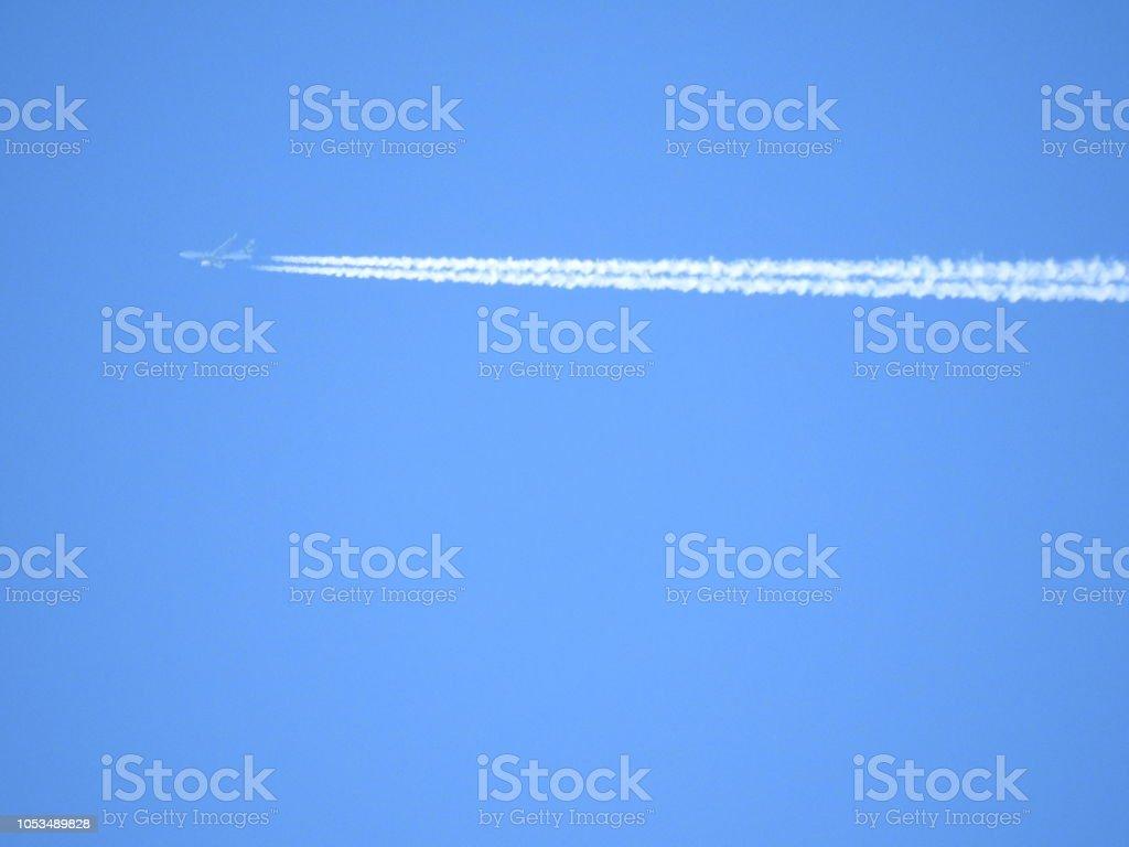 Un avion cruzando el cielo azul stock photo