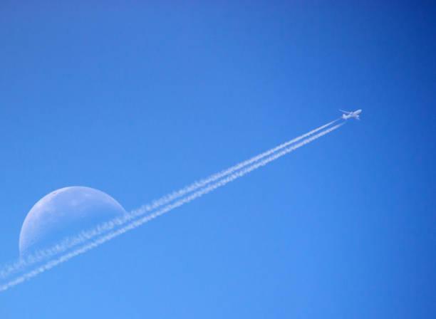 Plane flies past Moon stock photo