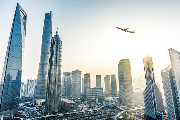 Plane fly over City A Plane fly over Shanghai. jin mao tower stock pictures, royalty-free photos & images