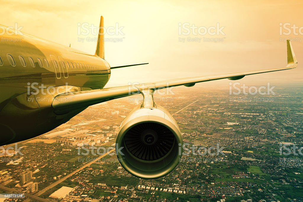 plane flyin above urban scene stock photo