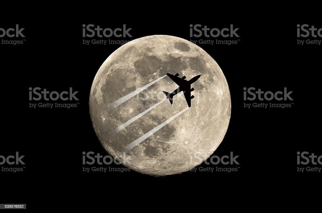 plane flying across the moon stock photo