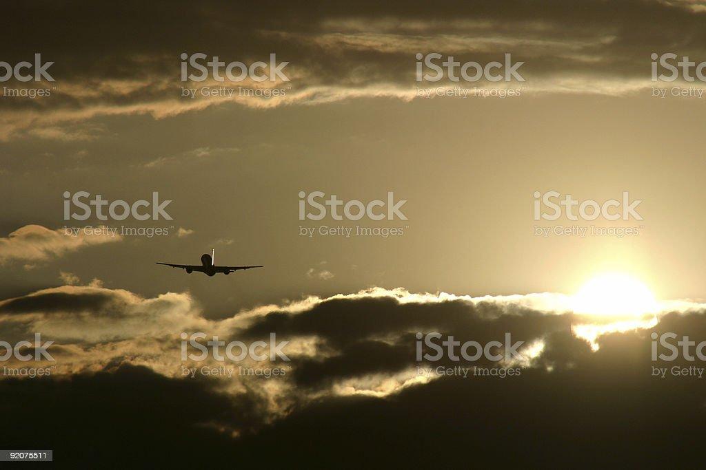 Plane flying into sunset royalty-free stock photo