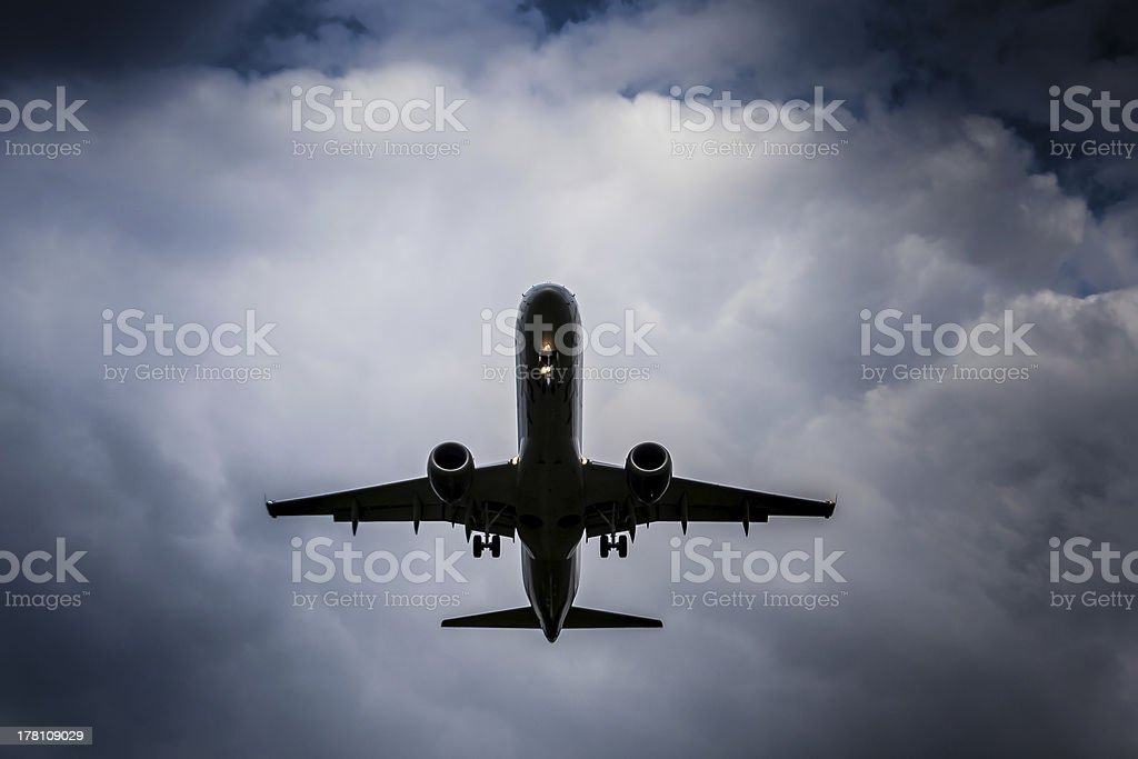 Plane flying on a cloudy day stock photo
