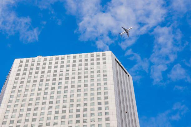 Plane flying over Nishishinjuku skyscrapers stock photo
