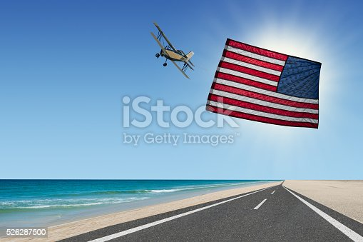 istock plane flying with american flag banner waving at beach 526287500