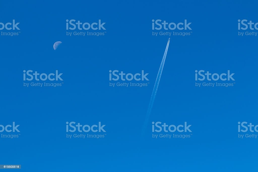 Plane in a clear sky and half moon stock photo