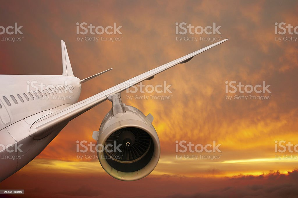 plane is flying at sunset stock photo