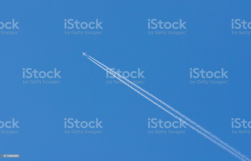 plane is flying on a blue sky stock photo