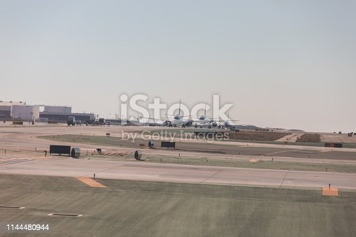 864534880 istock photo Plane landing and taxing in the runway of an airport 1144480944