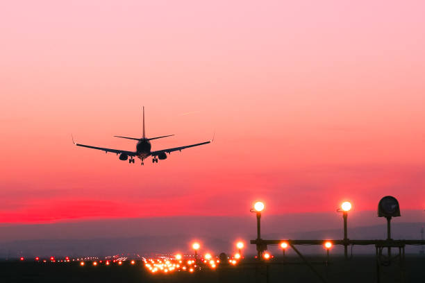 Plane lands at an airfield at the sunset stock photo