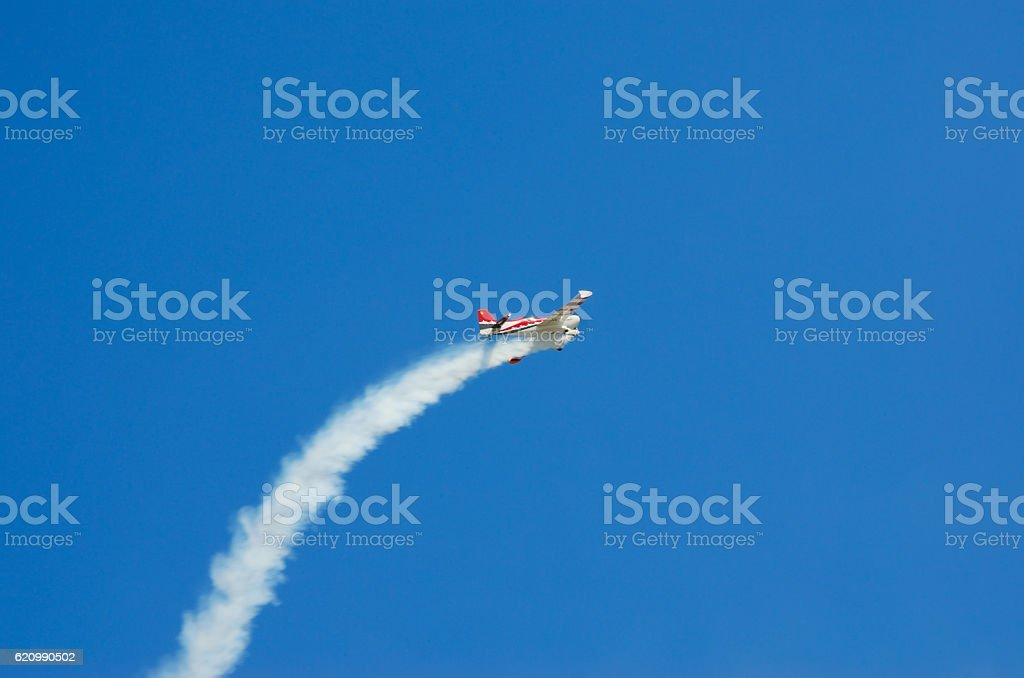 Plane left in trail of smoke in the blue sky. foto royalty-free