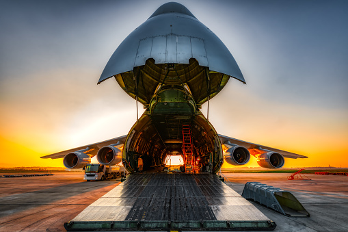 Plane on the ground with wide open freight room, fuel stop