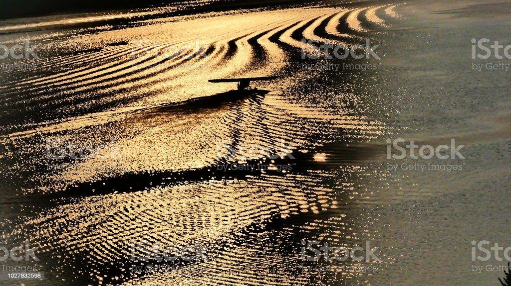 Avion sur l'eau avec le reflet du coucher de soleil sur les vagues stock photo