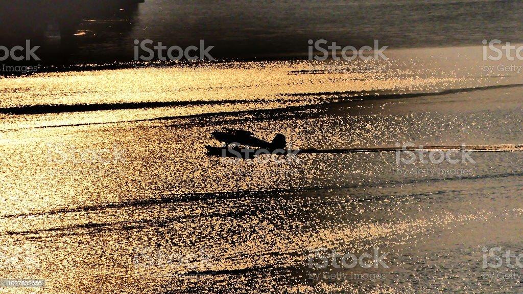 Avion sur l'eau avec le reflet du coucher de soleil stock photo