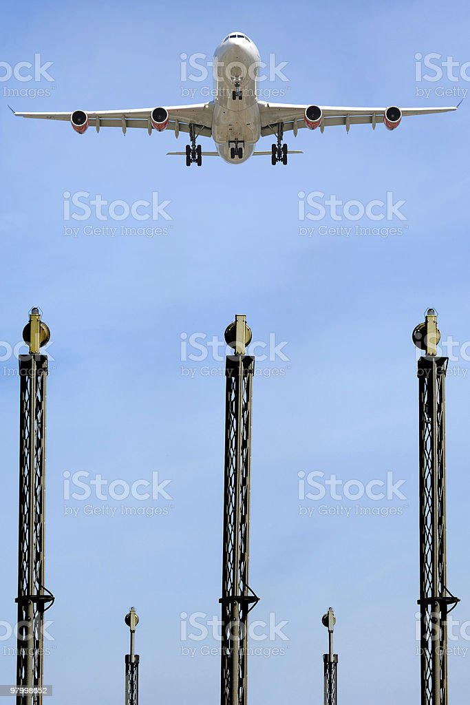Plane over lights in airport royalty-free stock photo