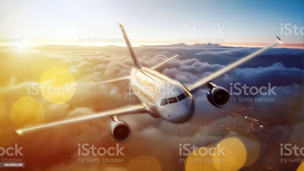 Plane over the clouds at dusk stock photo