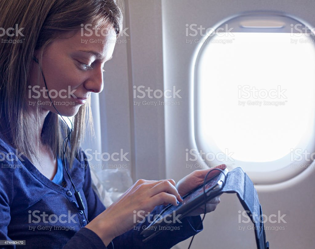 Plane Passenger In Airplane Using Tablet stock photo