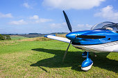 Light single prop aircraft plane closeup abstract parked on rural countryside farm grass airstrip runway between agriculture crops.