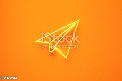 Plane symbol formed by yellow neon light on yellow background. Horizontal composition with copy space. Front view.