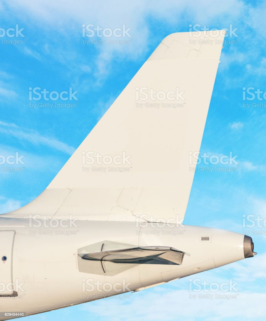Plane tail fin - sky with white clouds in background stock photo