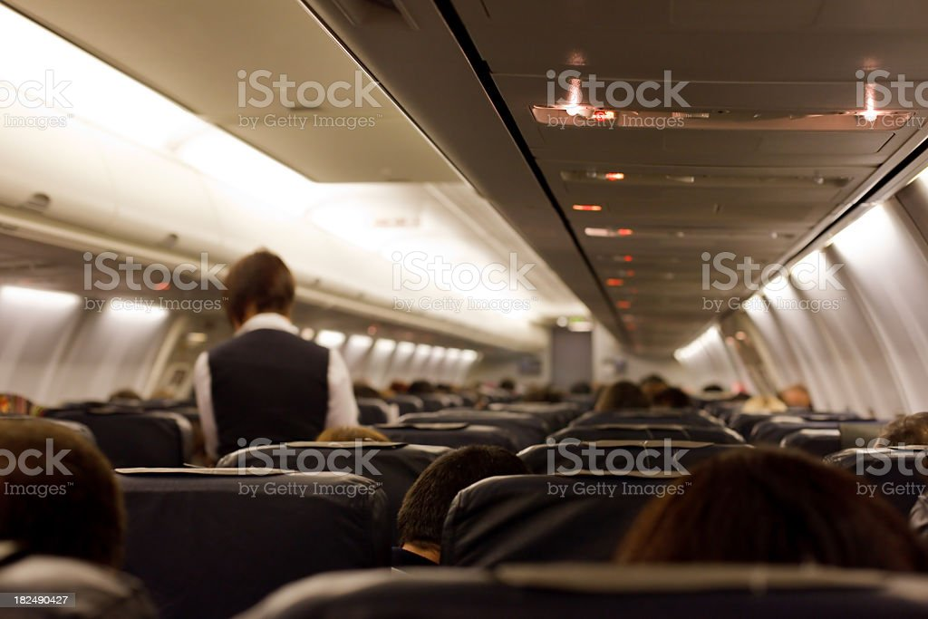 Plane taken from a seat with a stewardess in the isle stock photo