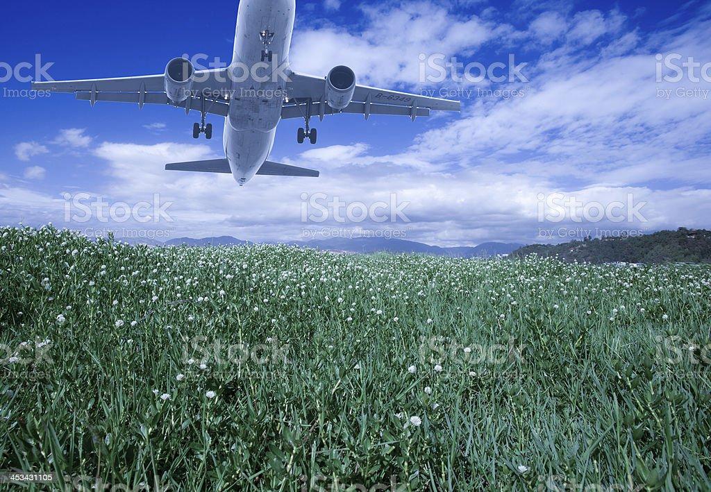 Plane takeoff over grassland stock photo