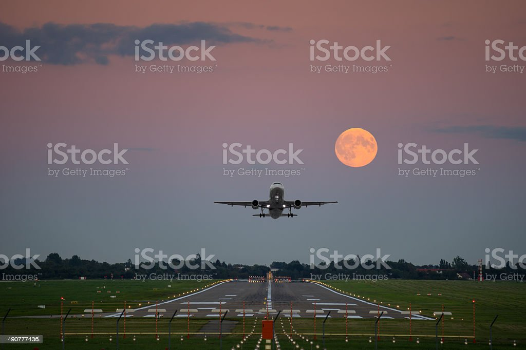 Plane take-off under the full moon stock photo