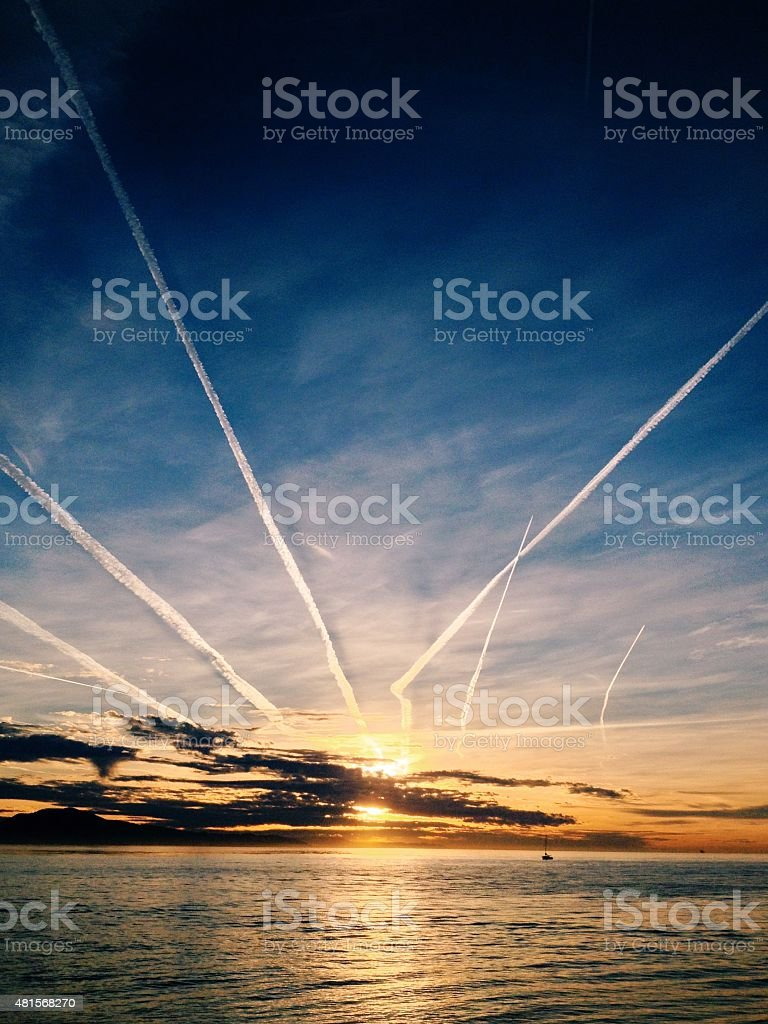 Plane trails, contrails in the sky over the ocean stock photo